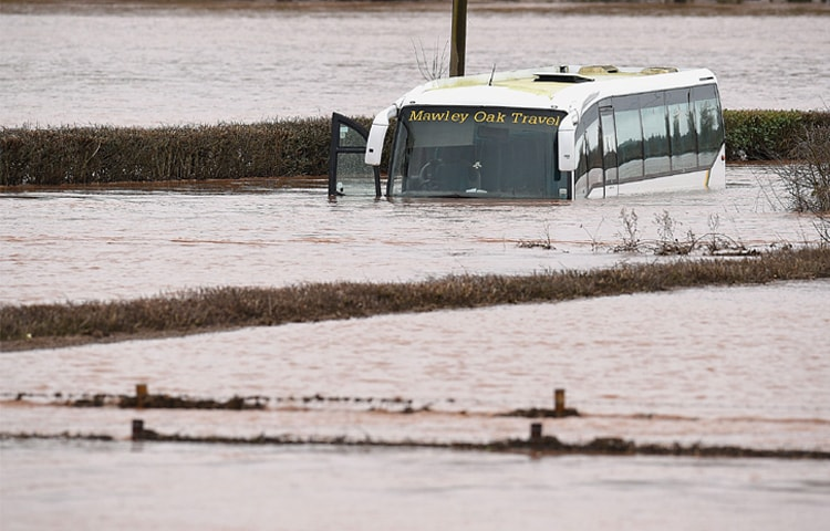 LINDRIDGE: An empty coach sits abandoned after the River Teme burst its banks near this town in western England on Sunday.—AFP