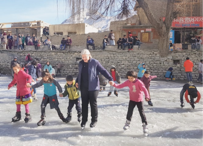 Canadian High Commissioner Wendy Gilmour trains local children in skating on a frozen pool in Hunza. —Dawn
