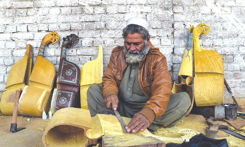 A worker makes a traditional rabab musical instrument at a workplace on the outskirts of Peshawar.—AFP