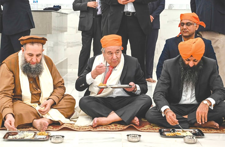 United Nations Secretary General Antonio Guterres eats food along with Minister for Religious Affairs Noorul Haq Qadri during his visit to the Baba Guru Nanak Dev shrine at Gurdwara Darbar Sahib in Kartarpur on Tuesday.—AFP