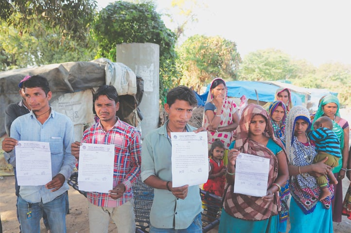 AHMEDABAD: Residents of a slum near Sardar Patel Gujarat Stadium hold eviction notices served to them.—AP