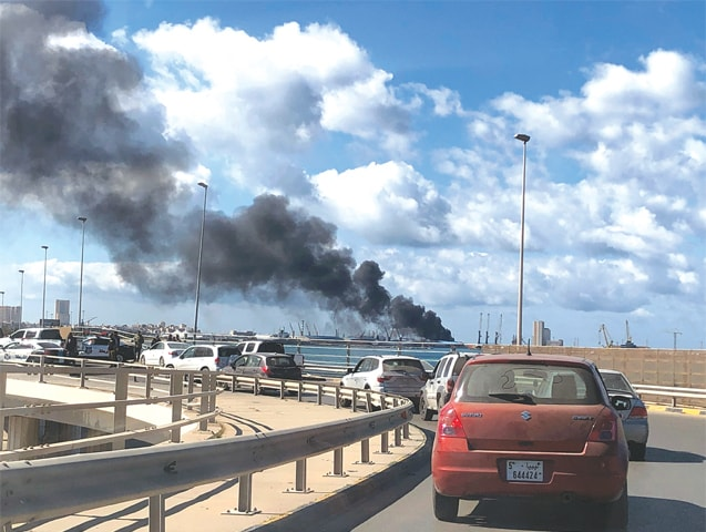 TRIPOLI: Smoke rises from the port after it was attacked on Tuesday.—Reuters