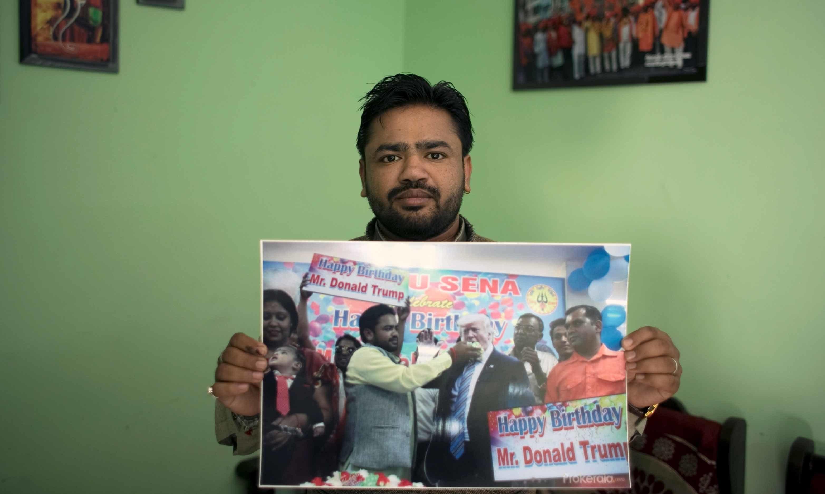 Vishnu Gupta, President of Shiv Sena, a Hindu hardline group, shows a picture of him celebrating US President Donald Trump's birthday, at his residence in New Delhi, India on February 13. — Reuters