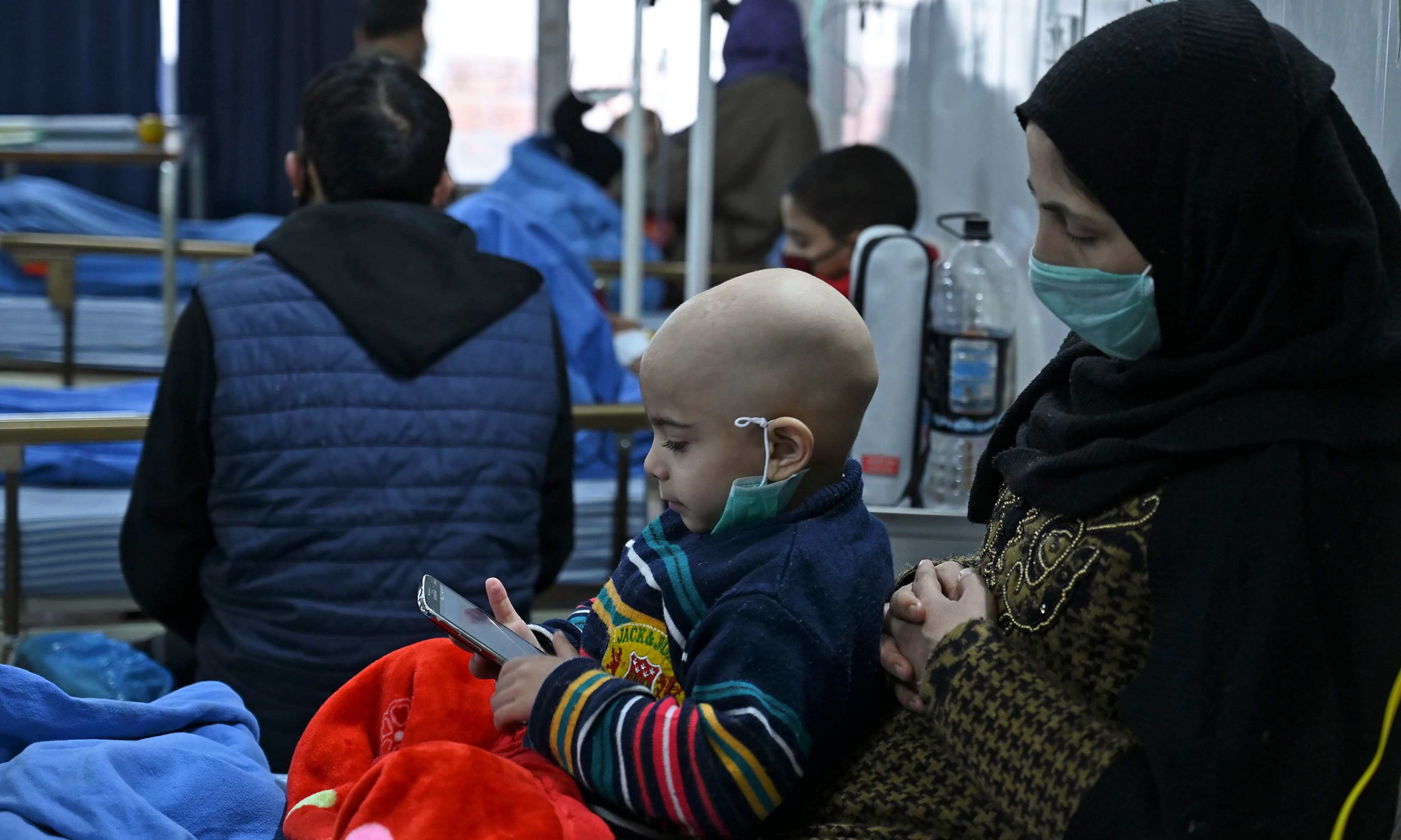 A mother holds her child who has cancer, inside a ward in a hospital in Srinagar. — AFP