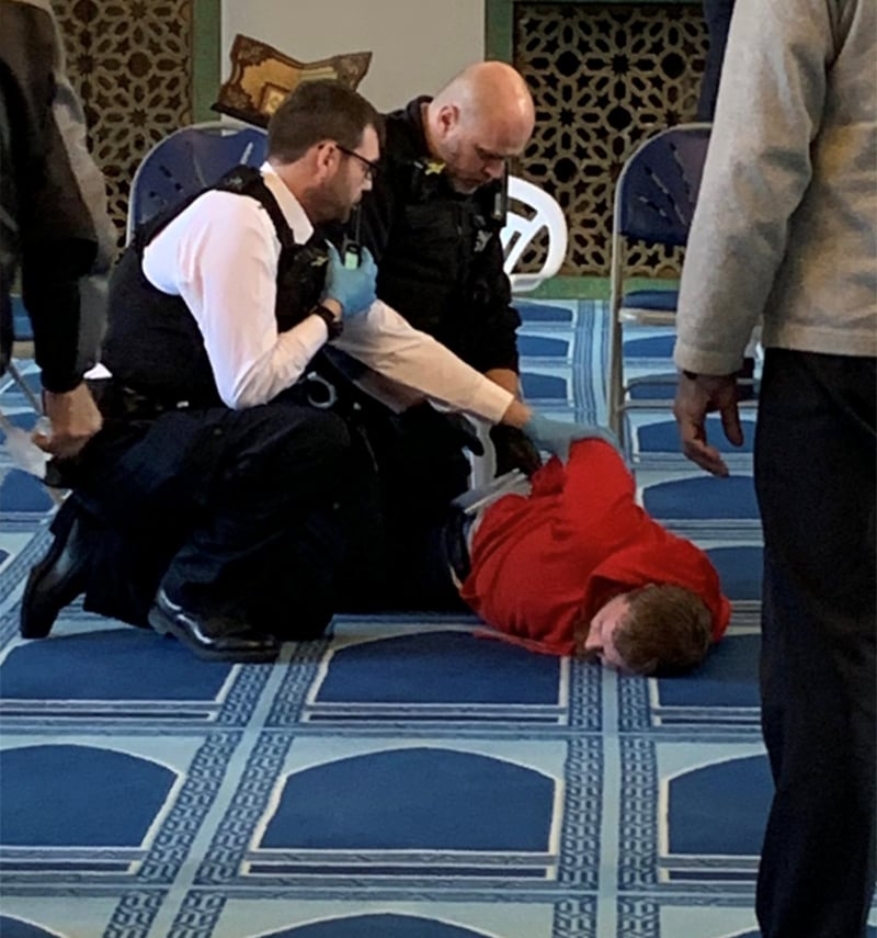 Police officers handcuff a man inside the London mosque. — Courtesy @MurshHabib Twitter