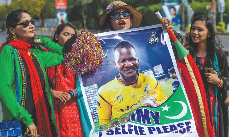 FANS carry a poster of Peshawar Zalmi captain Darren Sammy outside the National Stadium on the eve of the match between Peshawar Zalmi and Karachi Kings.—AFP