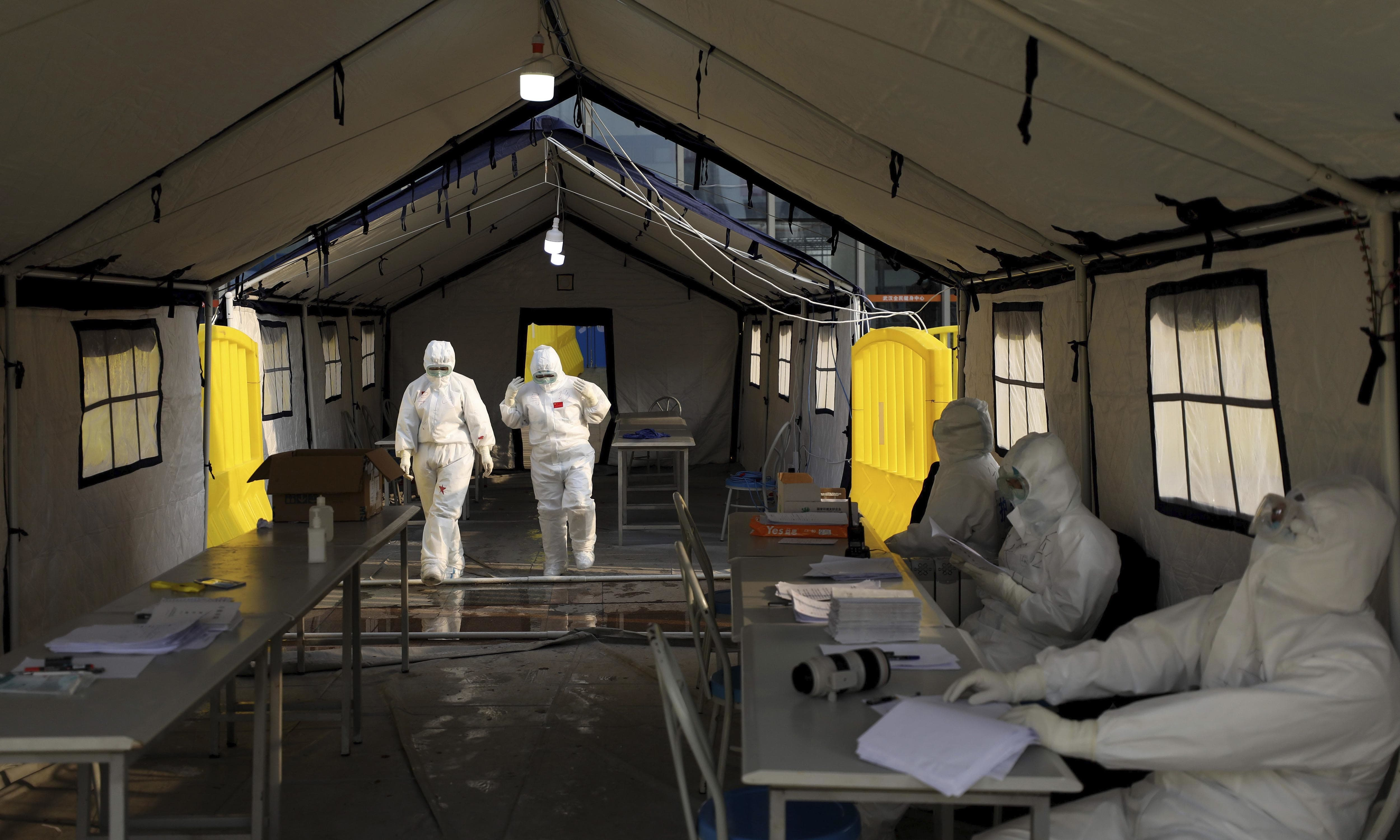 Medical workers in protective suits walk through a check-in tent at a temporary hospital at Tazihu Gymnasium in Wuhan on Feb 21. — AP