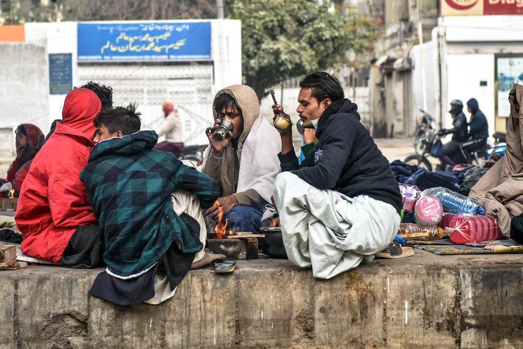 Men sit around a makeshift bonfire and consume tea during Karachi's winter | Fahim Siddiqi/White Star
