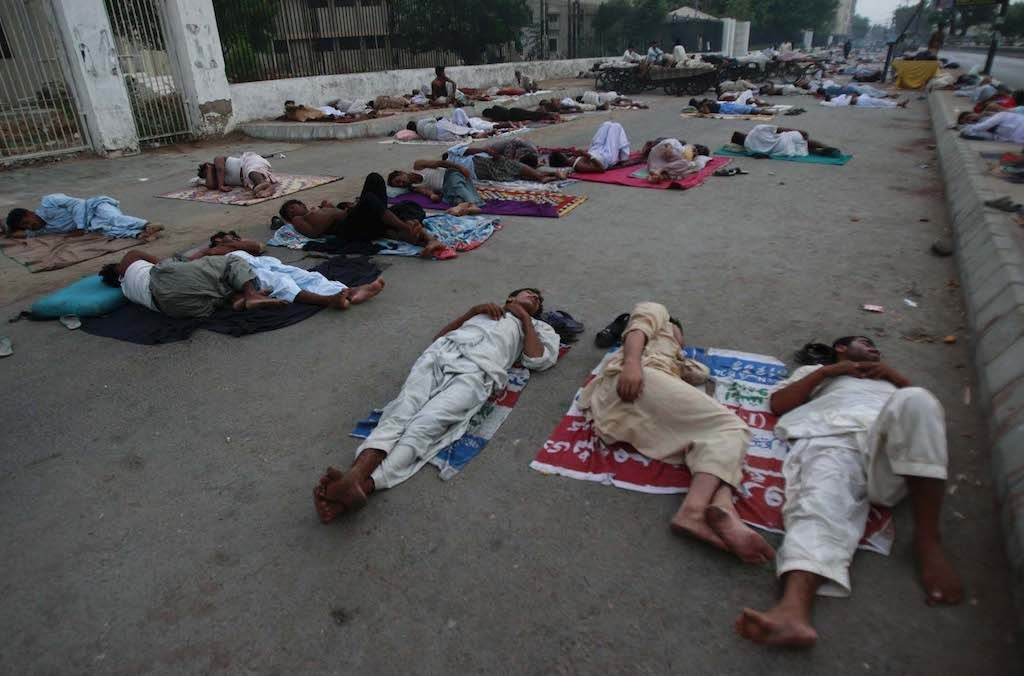 Men sleep on bedding and Panaflex materials on a road in Karachi | White Star