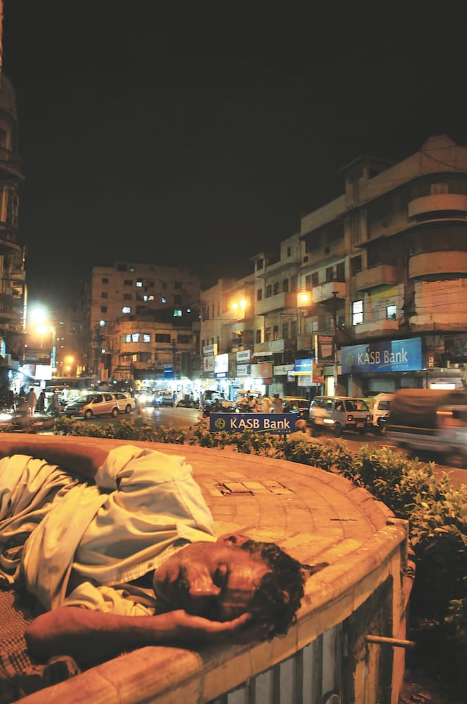 A homeless man sleeps on a pavement in Saddar | Stephan Andrew/White Star