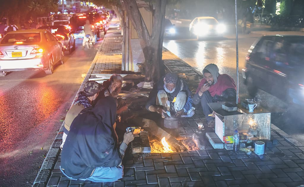 Men have dinner on a footpath by a busy road in Karachi | White Star