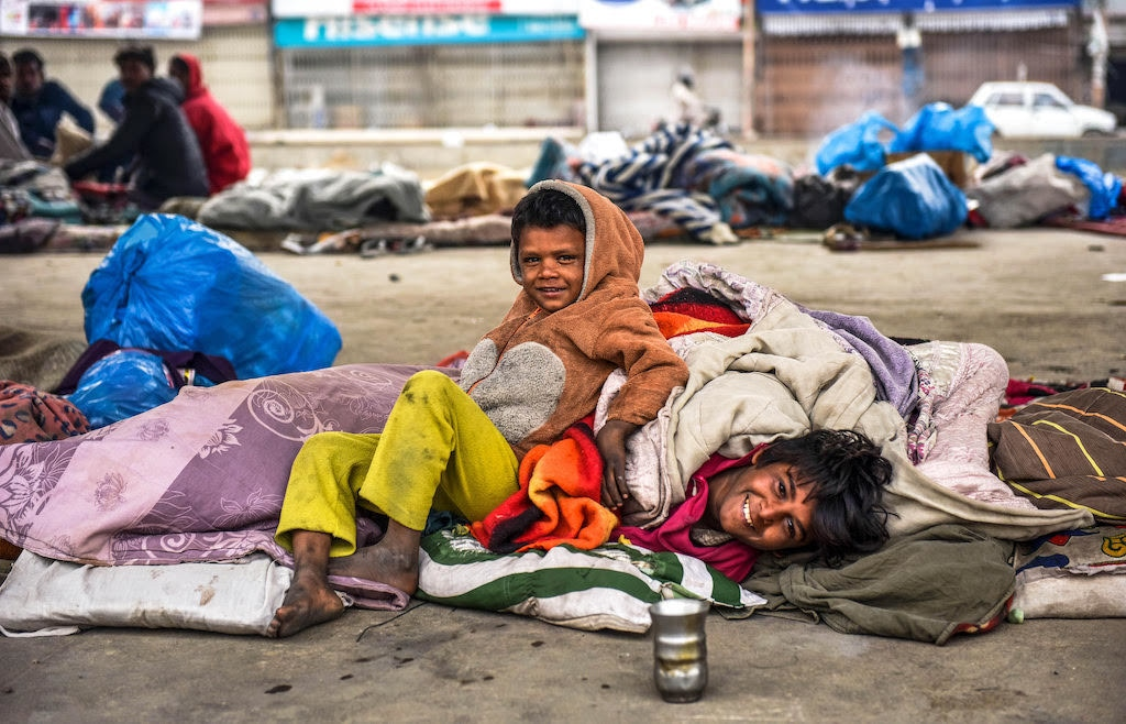 Two children smile for the camera while lying down on a pavement | White Star