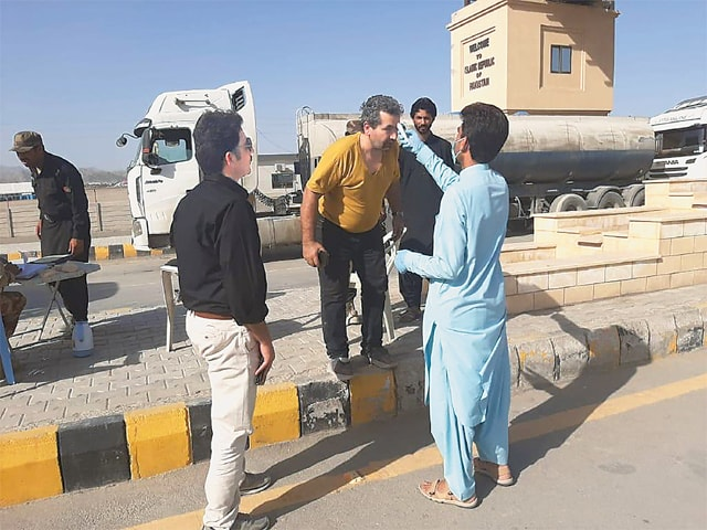 DOCTORS deployed at Taftan border screening a man after he crossed into Pakistan from Iran on Saturday. —Dawn