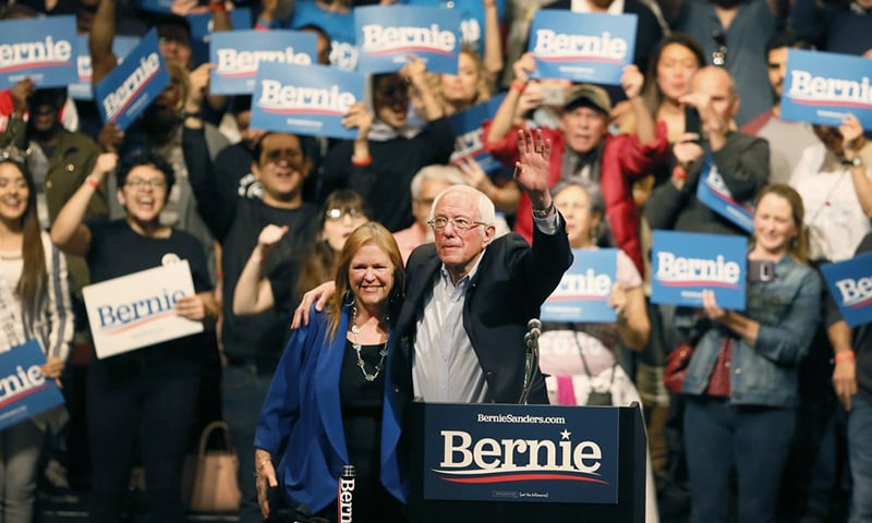 Standing next to his wife Jane O'Meara Sanders, Democratic presidential candidate Senator Bernie Sanders waves his hand during a rally in El Paso, Texas on Saturday. — AP