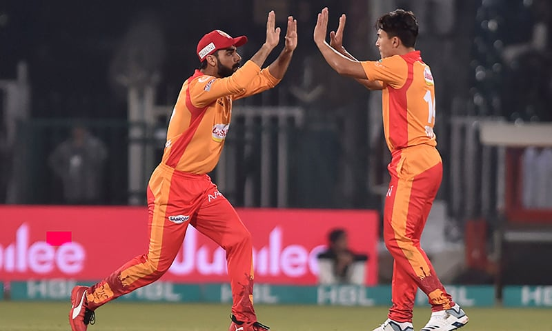 Islamabad United Muhammad Musa (2R) celebrates with a teammate after the dismissals of Lahore Qalandars Chris Lynn (unseen) during the Pakistan Super League (PSL) T20 cricket match betweenIslamabad United and Lahore Qalandars at the Gaddafi Cricket Stadium in Lahore on February 23, 2020.— AFP