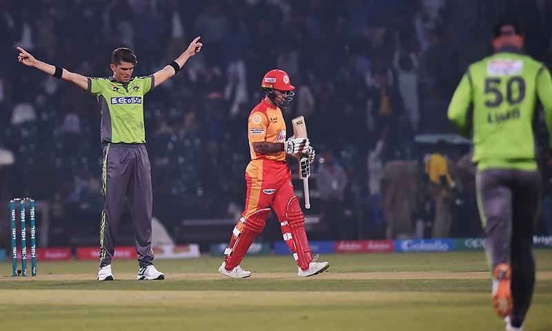 Lahore QalandarsShaheen Afridi (L) celebrates the wicket of Islamabad UnitedLuke Ronchi (C) walks back to the pavilion during the Pakistan Super League (PSL) T20 cricket match betweenIslamabad United and Lahore Qalandars at the Gaddafi Cricket Stadium in Lahore on February 23, 2020.— AFP
