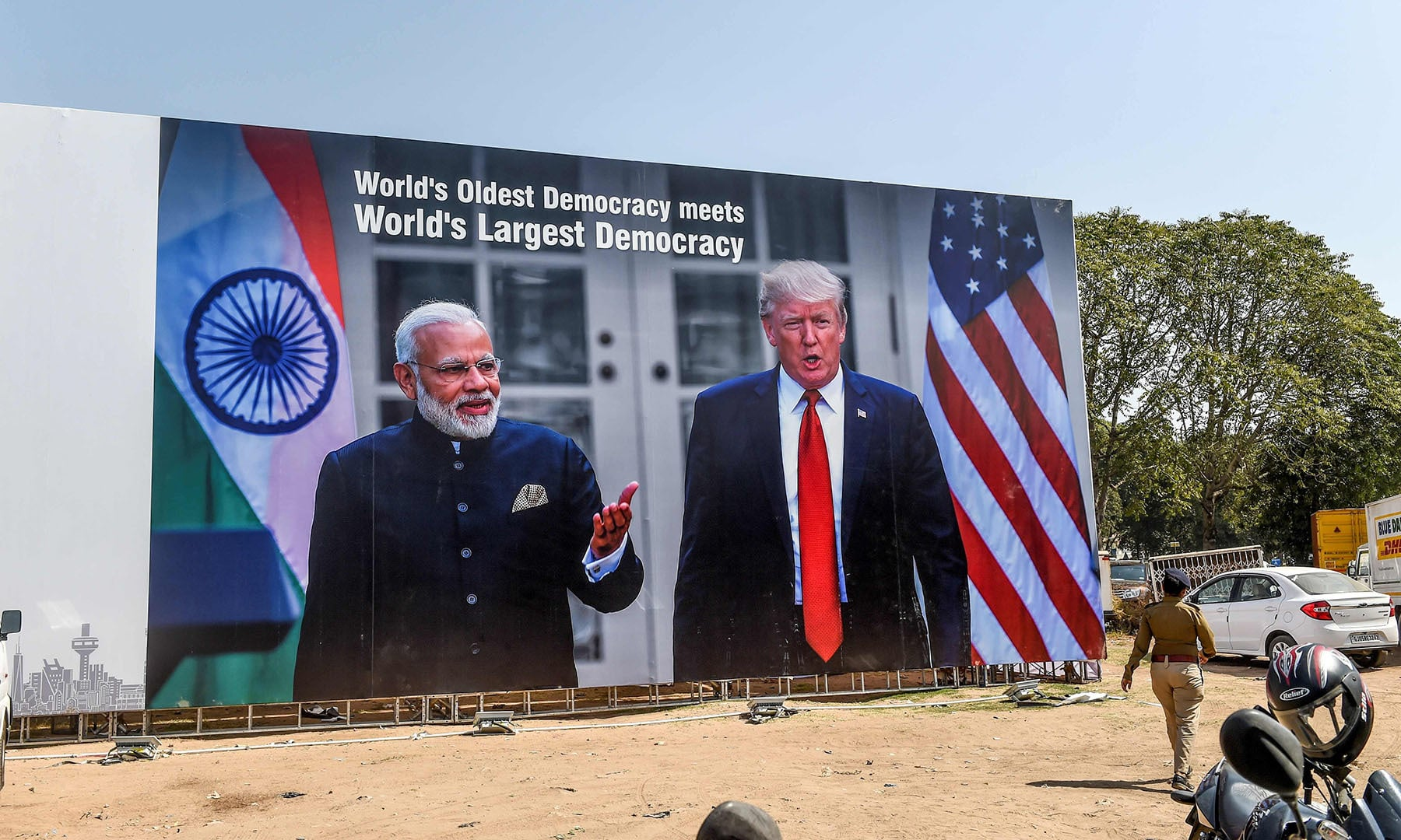 In this photo taken on February 22, a police personnel (R) walks past a billboard displaying pictures of India's Prime Minister Narendra Modi (L) and US President Donald Trump (R) near the Sardar Vallabhbhai Patel International Airport in Ahmedabad, ahead of US President Donald Trump's visit in India.  — AFP