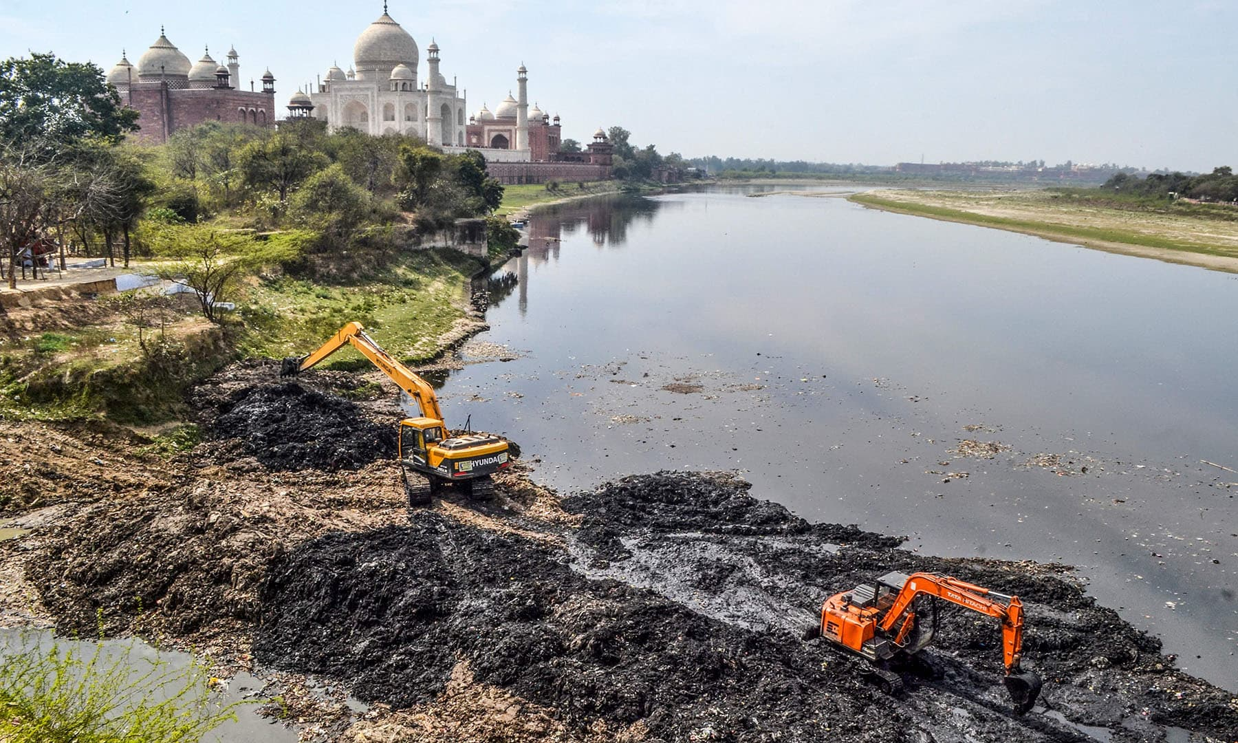 In this photo taken on February 19, Agra Municipal Corporation workers use excavators to clean the banks of the Yamuna river behind the Taj Mahal in Agra, ahead of the US President Donald Trump's visit in India.  — AFP
