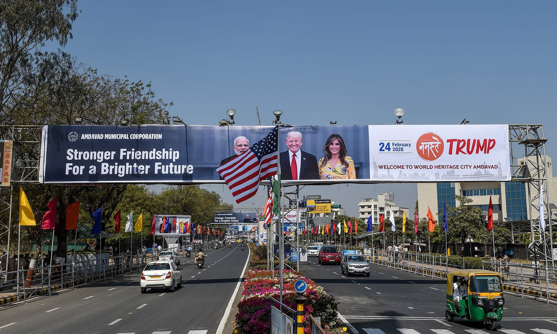 In this photo taken on February 22, US and Indian national flags wave in front of a billboard displaying pictures of India's Prime Minister Narendra Modi (L) and US President Donald Trump (C) and his wife Melania (R) near the Sardar Vallabhbhai Patel International Airport in Ahmedabad, ahead of US President Donald Trump's visit in India. — AFP