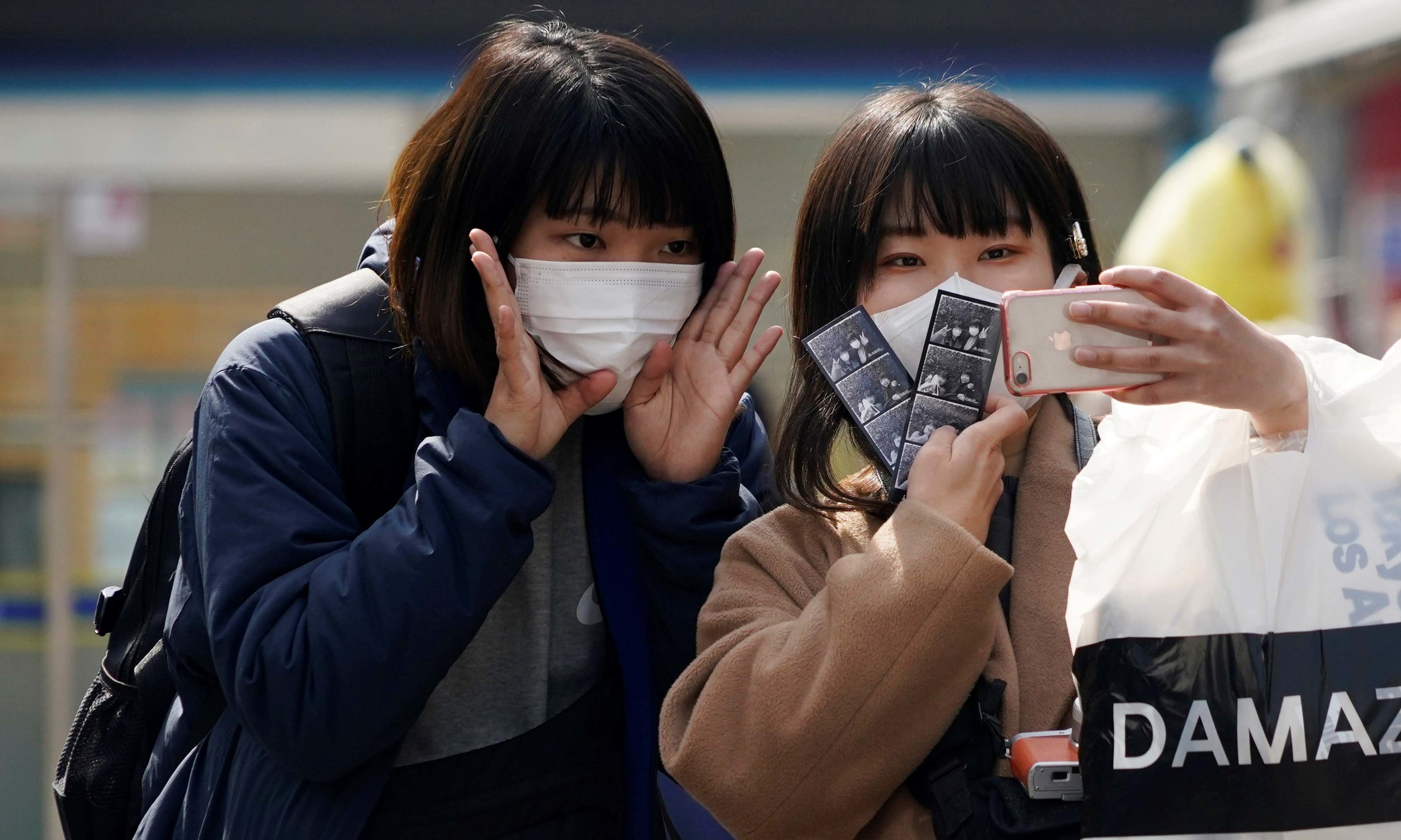 Tourists wearing masks to prevent the coronavirus take a selfie at a shopping district in Seoul, South Korea, February 24. — Reuters