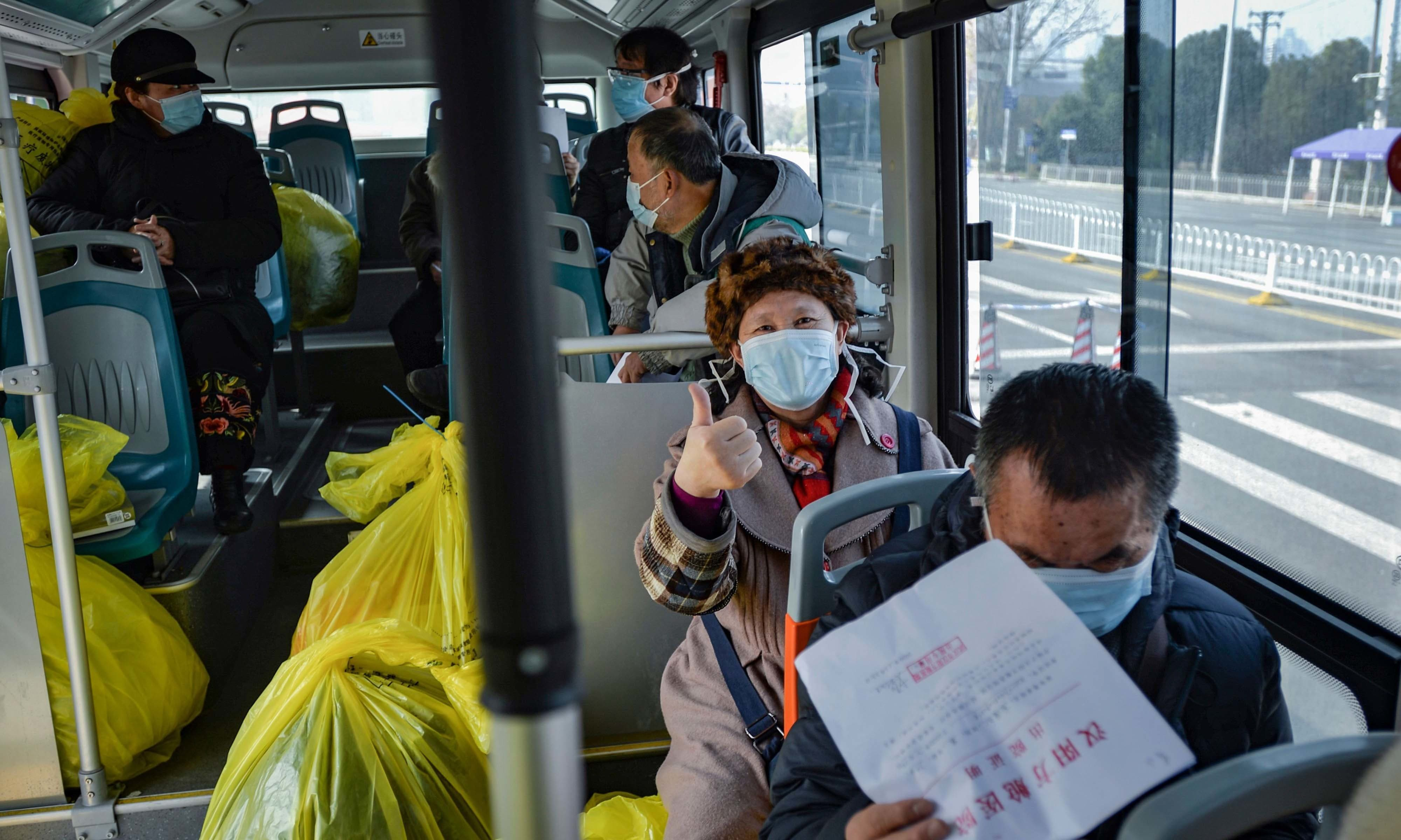 This photo taken on February 22, 2020 shows people who have recovered from the COVID-19 coronavirus infection leaving a hospital by bus in Wuhan in China's central Hubei province. — AFP/File