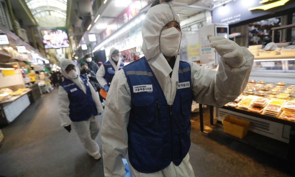 Workers wearing protective gears arrive to spray disinfectant as a precaution against the coronavirus at a market in Seoul, South Korea, on Feb 24. — AP