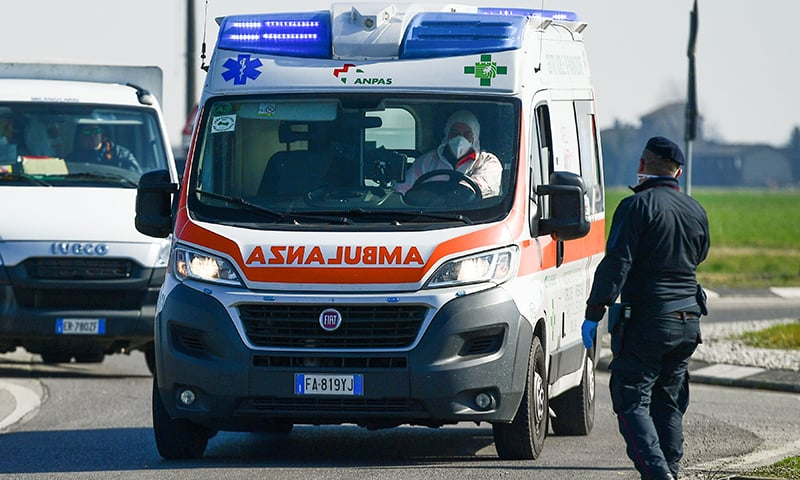 """An ambulance drives past a police check-point a few kilometres from the small town of Castiglione d'Adda, southeast of Milan, Italy on Monday. The country has established """"red zones"""" in 11 towns in its northern part to try and control the outbreak of COVID-19. — AFP"""