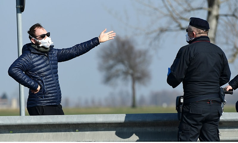 An Italian police officer talks with an inhabitant wearing a respiratory mask at a check-point a few kilometres from the small town of Castiglione d'Adda, southeast of Milan.  Police have established checkpoints to monitor movement in the red zone areas of the country. — AFP