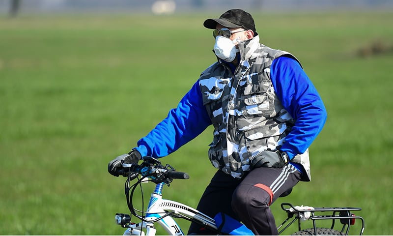 A cyclist wearing a mask in northern Italy. The Italian police has cordoned off areas in the northern part of the country putting more than 50,000 people in isolation in efforts to control the spread of COVID-19 in the country. — AFP