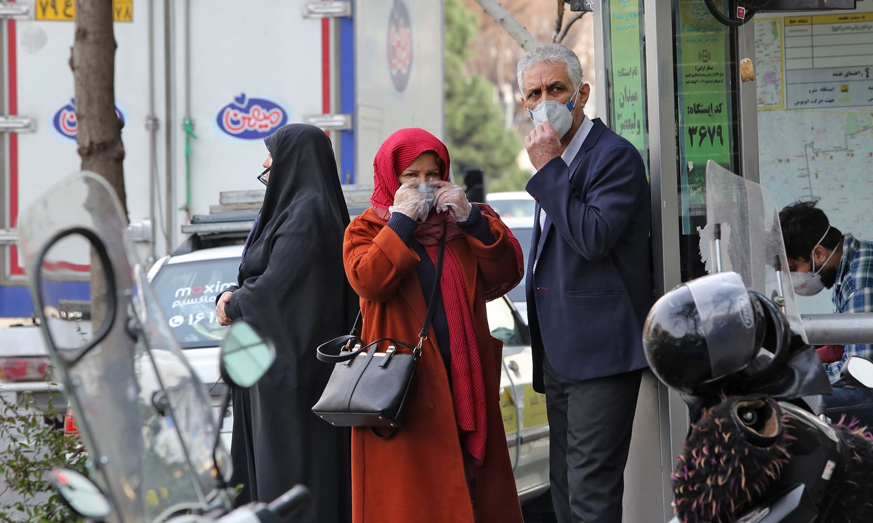 People wearing protective masks wait along the side of a street in the Iranian capital on Feb 24. — AFP