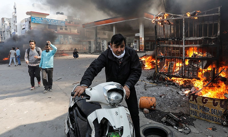 A man pushes his damaged scooter past a burning petrol pump during a clash between people supporting a new citizenship law and those opposing it, in New Delhi India on February 24. — Reuters