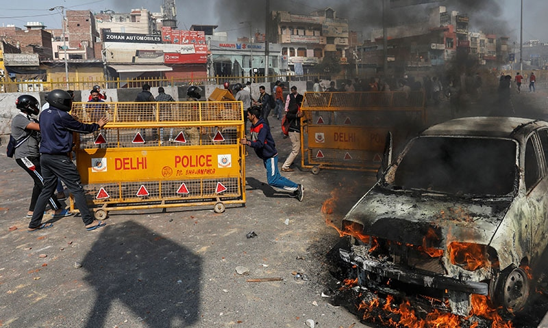 People supporting a new citizenship law push police barricades during a clash with those opposing the law in New Delhi, India, on February 24. — Reuters