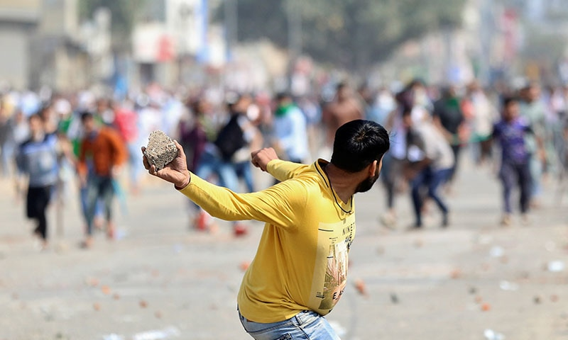 A man supporting a new citizenship law throws a stone at those who are opposing the law, during a clash in New Delhi, India on February 24. — Reuters