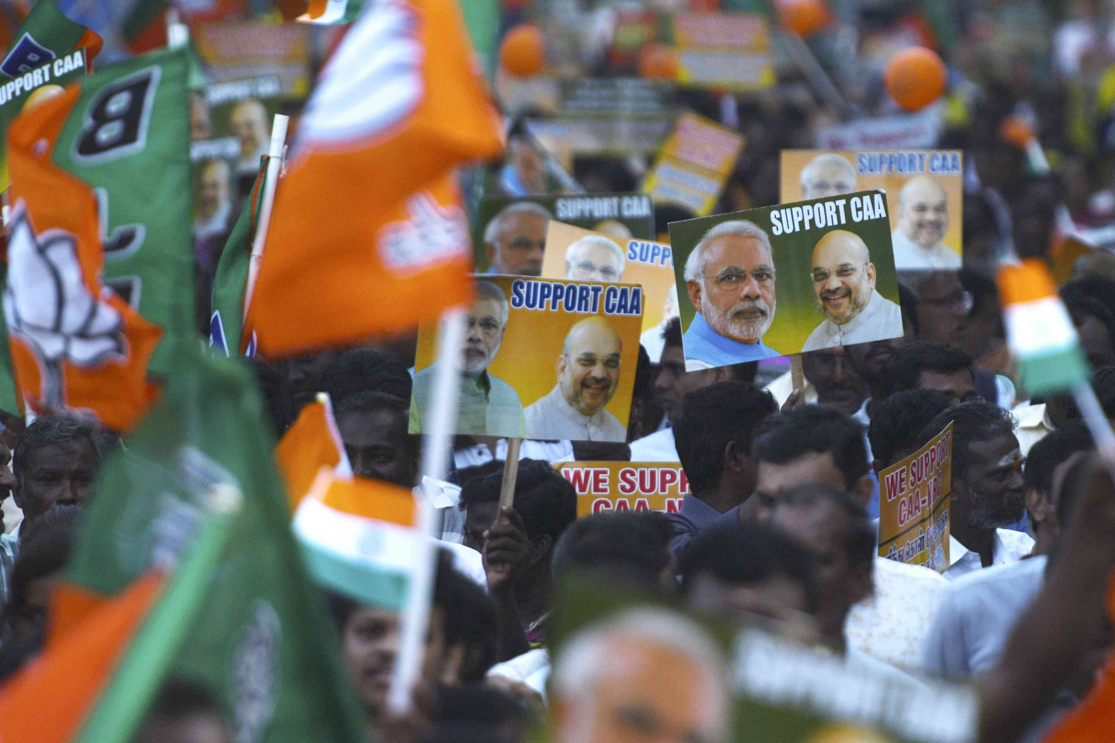 Supporters of the Bharatiya Janata Party wave party flags and hold placards in support of the government's Citizenship Amendment Act and the National Register of Citizens during a rally in Chennai on January 7. Credit: AFP