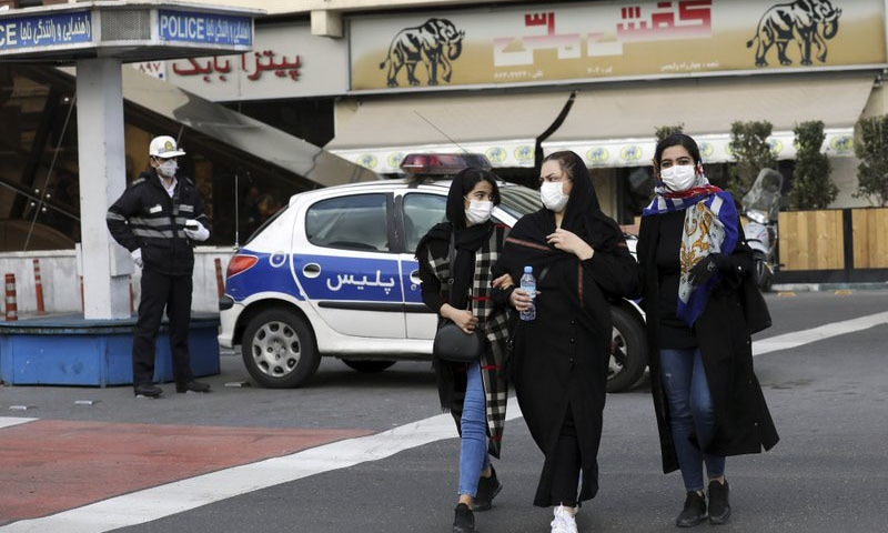 A policeman and pedestrians wear masks to help guard against the Coronavirus, in downtown Tehran, Iran, on Sunday. — AP