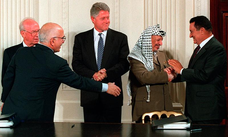 مصر کے سابق صدر اس یادگار تصویر میں فلسطینی رہنما یاسر عرفات سے مصافحہ کر رہے ہیں، اس موقع پر امریکی صدر بل کلنٹن، اسرائیلی وزیر اعظم یٹژاک رابن اور اردن کے بادشاہ حسین بھی موجود ہیں— فوٹو: اے ایف پی