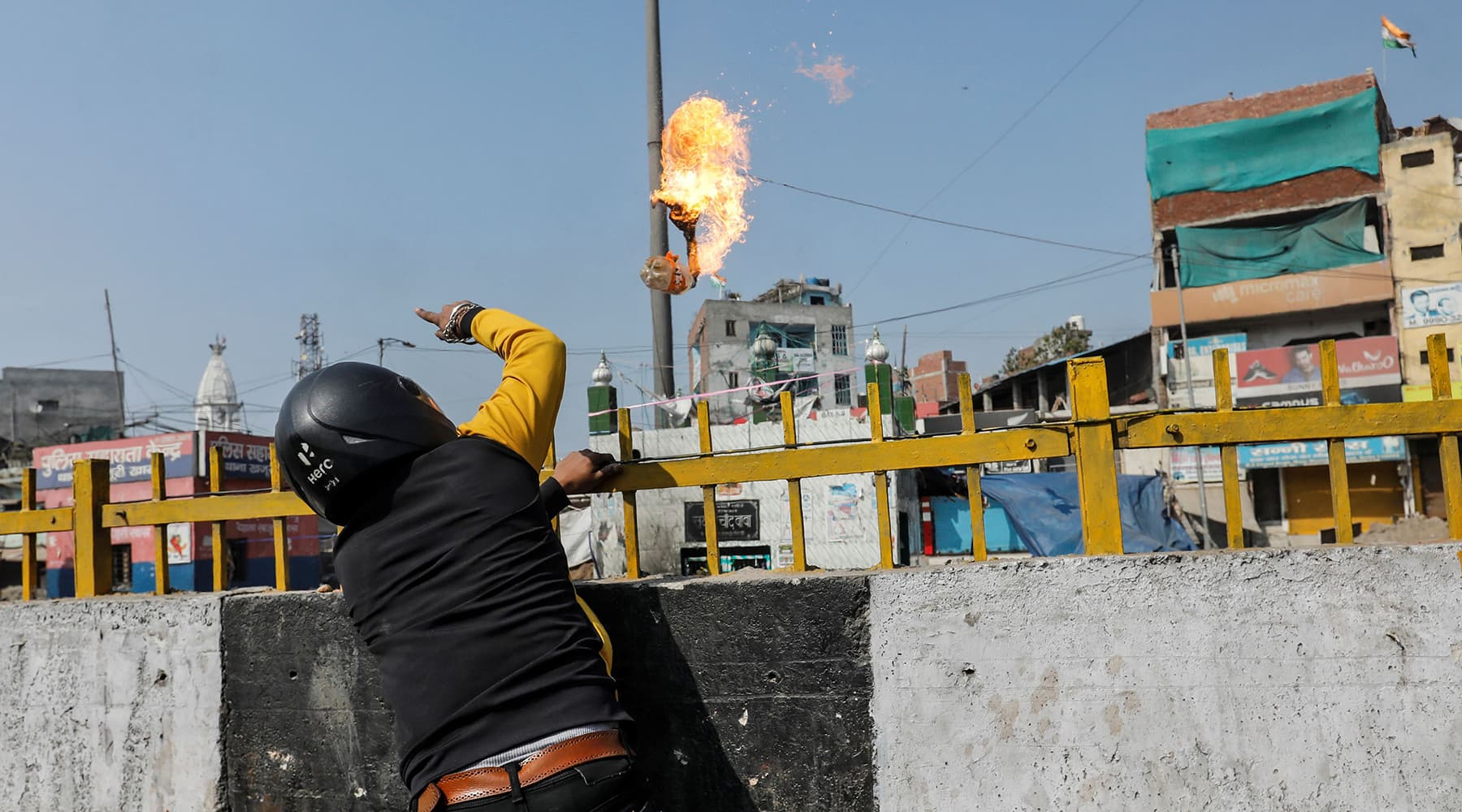 A man supporting the new citizenship law throws a petrol bomb at a Muslim shrine during a clash with those opposing the law in New Delhi India on Monday. — Reuters