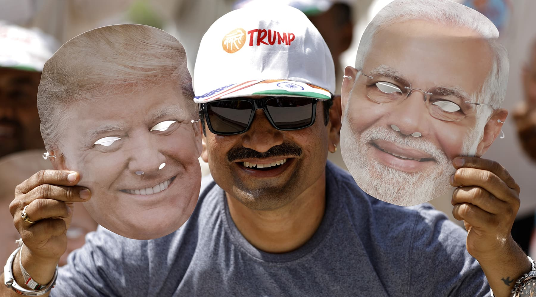 """A man holds masks depicting US President Donald Trump and Indian Prime Minister Narendra Modi during the """"Namaste Trump"""" event attended by Trump and Modi at Sardar Patel Gujarat Stadium, in Ahmedabad, India. — Reuters"""
