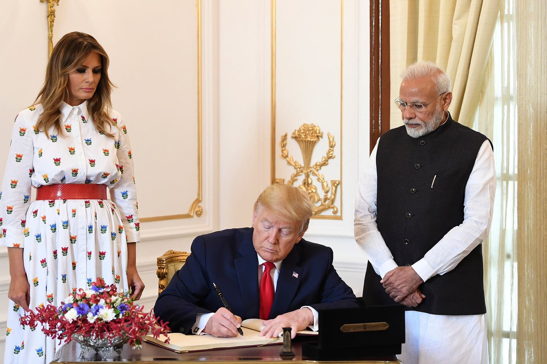 US President Donald Trump signs the visitor's book as First Lady Melania Trump and India's Prime Minister Narendra Modi look on at Hyderabad House in New Delhi. — AFP/MEA