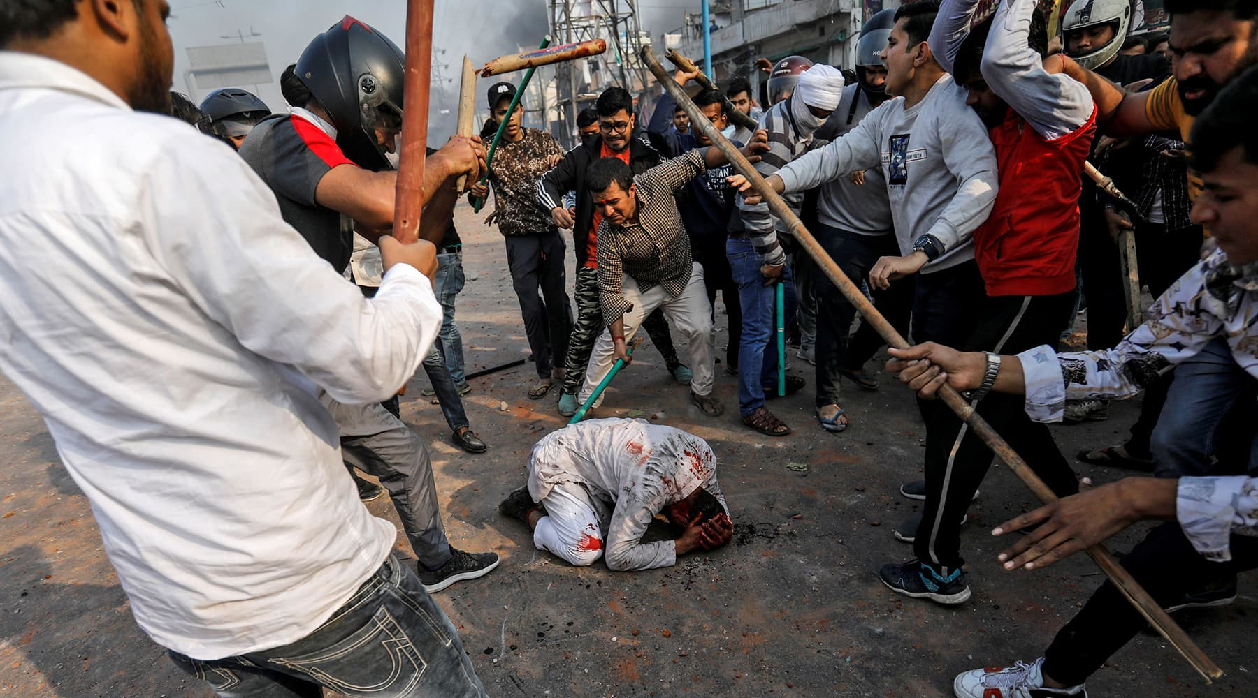 People supporting the new citizenship law beat a Muslim man during a clash with those opposing the law in New Delhi, India on Feb 24. — Reuters