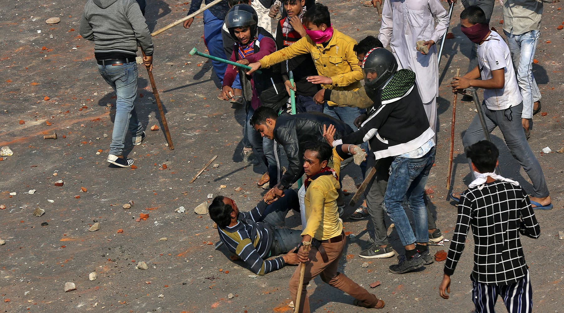 A man is beaten during a clash between people supporting a new citizenship law and those opposing the law in New Delhi, India on Feb 24. — Reuters