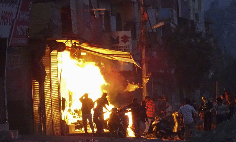 A shop is set on fire during violence between two groups in New Delhi, India, on Tuesday. — AP