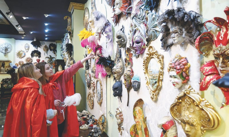 Shkoder (Albania): Visitors look for carnival masks in a salon of the Venice art mask workshop.—AFP