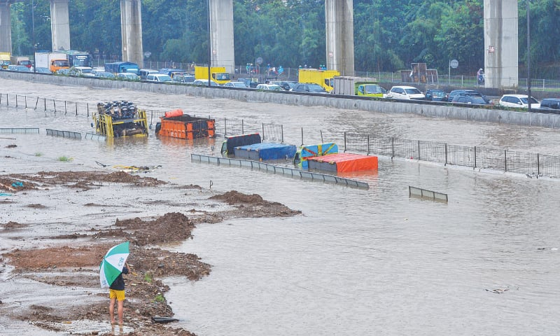 JAKARTA: Trucks are seen submerged along a highway on Tuesday.—Reuters