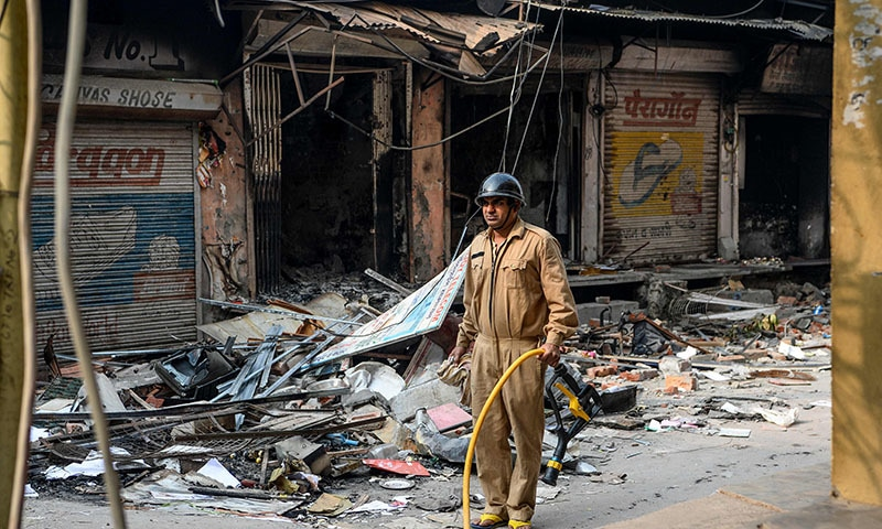 A firefighter stands holding a pipe on street near burnt-out premises following clashes between people supporting and opposing a contentious amendment to India's citizenship law in New Delhi on February 26. — AFP