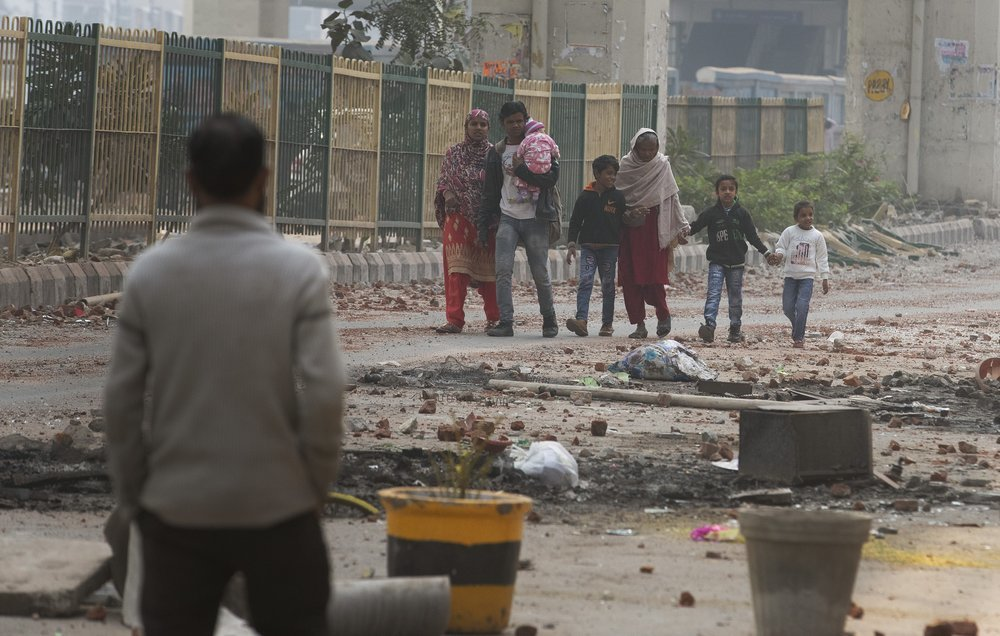 A family walks past a road littered with stones on Wednesday after Tuesday's violence in New Delhi, India. — AP