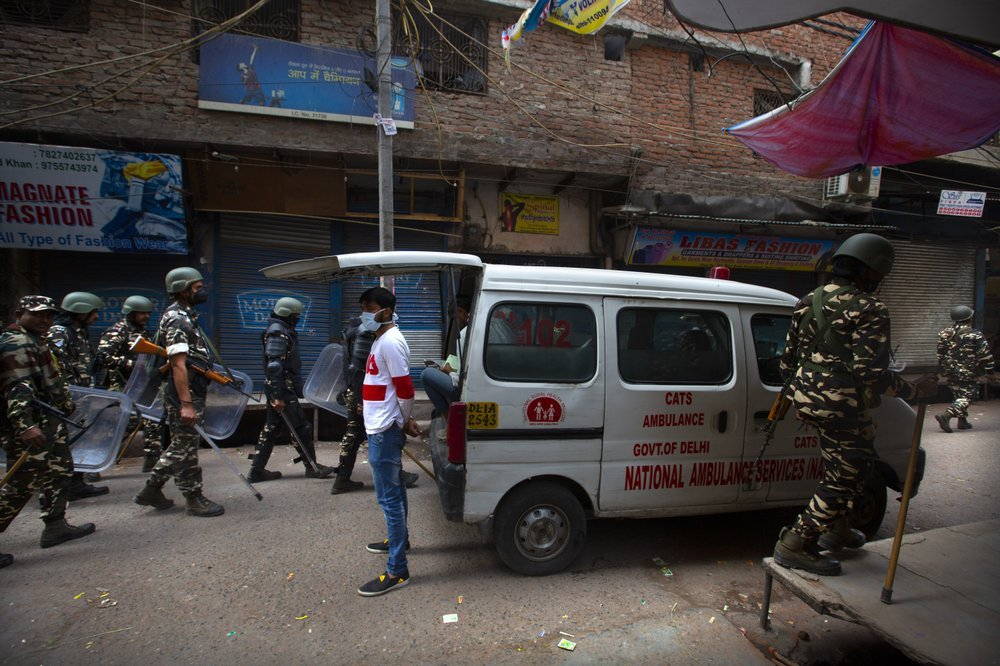 Indian paramilitary force soldiers patrol on Wednesday as an ambulance stationed at the area which witnessed Tuesday's violence in New Delhi, India. ─ AP