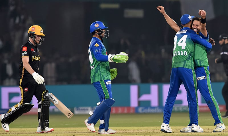 Multan Sultans's Shahid Afridi (R) celebrates with teammates after taking the wicket of Peshawar Zalmi's Liam Dawson (L) during the Pakistan Super League (PSL) Twenty20 cricket match at the Multan Cricket Stadium in Multan on February 26. — AFP