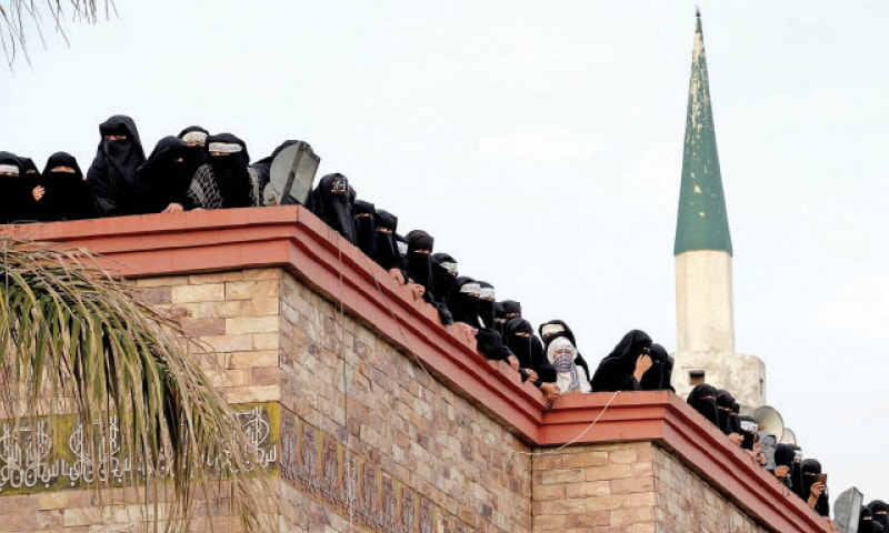 Jamia Hafsa students stand on the roof of Lal Masjid on Wednesday. — Photo by Mohammad Asim