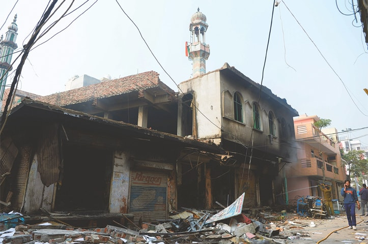 NEW DELHI: A man speaks on his mobile phone as he walks past a burnt-out mosque on Wednesday.—AFP